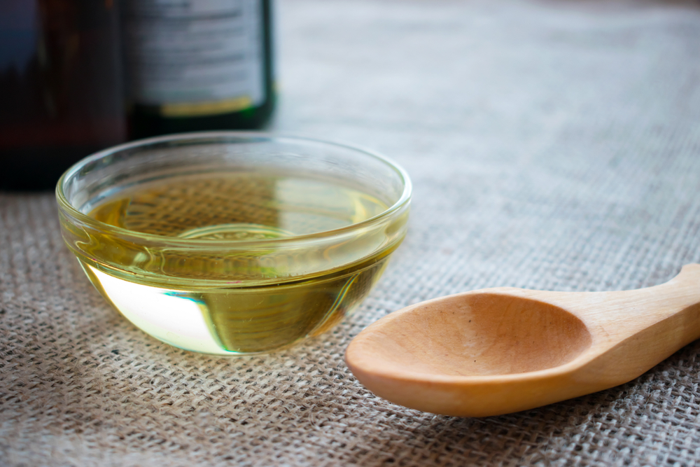 best mct oil image showing transparent glass bowl filled with oil, plus a wooden spoon next to it